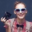 Portrait of beautiful hipster style young woman in white shirt and bow-tie. Old camera hanging by the neck — Stock Photo