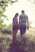 Walking loving couple at sunset — Stock Photo