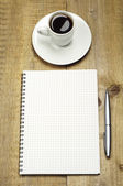Notepad, pen and cup of coffee — Stok fotoğraf