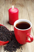 Cup of tea and dry black tea and candle — Stock Photo