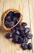 Dried plum in a basket and scattered — Stock Photo