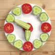 Cucumber and tomato in the shape of clock — Stock Photo