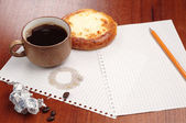 Coffee with bun, pencil and crumpled paper — Stockfoto