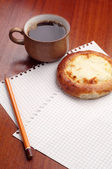 Sheet of paper, bun and coffee — Stock Photo