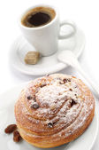Round bun and cup of coffee — Stock Photo