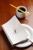 Notebook on a plate and coffee — Stock Photo