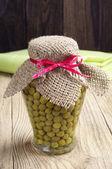 Green peas in glass jar — Stock Photo