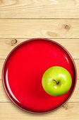 Green apple on a red plate — Stock Photo