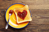 Toast bread with jam in shape of hearts — Stock Photo