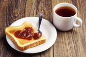 Tea and toast bread with jam in shape of hearts — Stock Photo