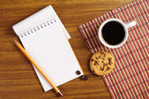 Notepad and coffee with cookies — Stockfoto