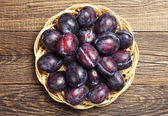 Plate with plums on table — Stock Photo