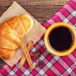 Постер, плакат: Coffee cup with a croissant
