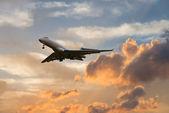 Airplane landing at sunset — Stock Photo