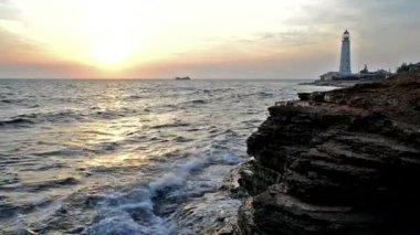 закат на каменистый берег, маяк на фоне — Стоковое видео