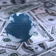 Digital earth globe on heap of dollars — Stock Photo