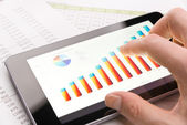 Analyzing graph with tablet-pc close-up — Stock Photo
