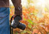 Photographer holding camera outdoors — Stock Photo