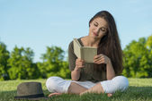 Beauty young woman with book in park — Stock Photo