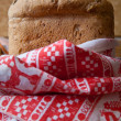 Fresh bread wrapped in a towel in a country style - Stock Photo