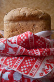 Fresh bread wrapped in a towel in a country style — Stock Photo