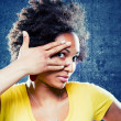 Afro womlooking through her fingers — Stockfoto #12683700