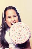 Little Girl Biting a Big Lollipop — Stock Photo