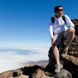 Young Man Having a Rest in a High Peak Over Clouds — Stock Photo