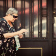 Stock Photo: Senior WomSelling Lottery Coupons in Street