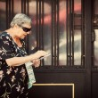 Senior Woman Selling Lottery Coupons in the Street — Stock Photo