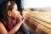 Little girl looking through window. She travels on a train. — Stock Photo