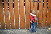 Young boy standing on wooden fence — Foto Stock
