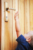 Little boy try to reach door-handle — Stock Photo