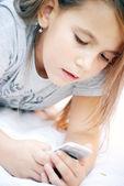 Little girl looks on mobile phone — Stock Photo