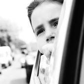 Hermosa niña en el coche mirando la ventana de tiro. a la espera de la luz roja — Foto de Stock