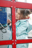 Little girl in public telephone — Foto Stock