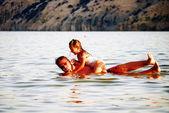 Padre e hija jugando en el mar — Foto de Stock