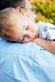 Little boy sleeping on dad's shoulder — Stock Photo