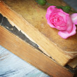 Rose on old blue wooden table with old books — Stock Photo