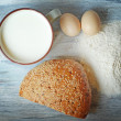 Milk, bread, eggs, flour and wheat on a vintage wooden background — ストック写真