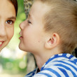 Little boy whispering to a little girl — Stock Photo
