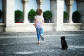Little boy playing with dog in the city — Stok fotoğraf