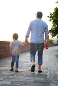Man with son walking and holding hands — Foto Stock