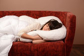 Happy young girl slipping on sofa — Stock Photo