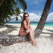 Young beautiful woman sitting on the palm tree — Stock Photo