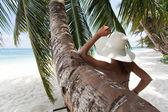 Giovane ragazza appoggiata su una spiaggia — Foto Stock