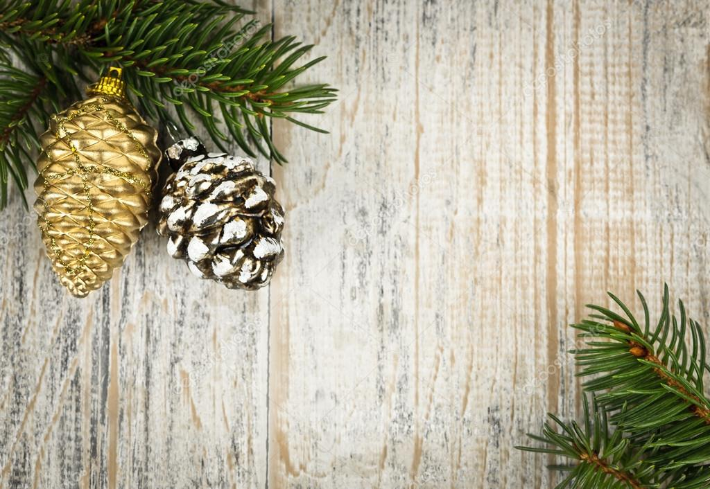 Christmas golden balls and pine cone on spruce branch with wooden background — Stock Photo #16767317