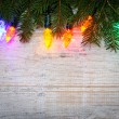 Christmas background with lights on branches - Stock Photo