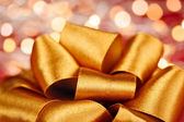 Gold gift bow with festive lights — Stock Photo