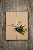 Christmas present in brown paper tied with string — Stock Photo